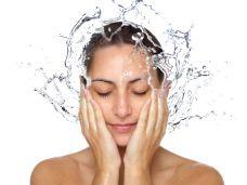 Frau wäscht sich mit Wasser das Gesicht