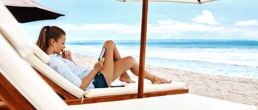Frau am Strand liegt auf Liege unter Sonnenschirm