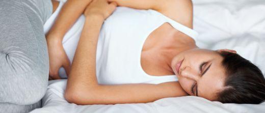 Frau krümmt sich auf Bett