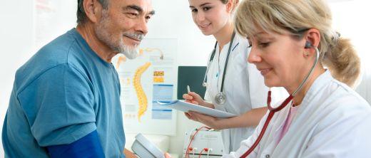 Ärztin misst Blutdruck eines Patienten