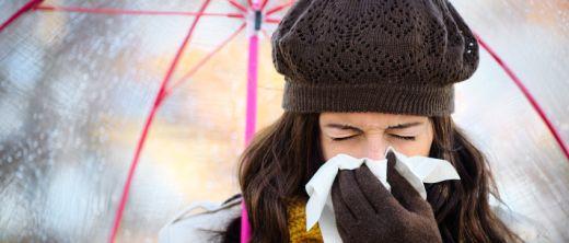 erkältung frau mit schirm schnäuzt