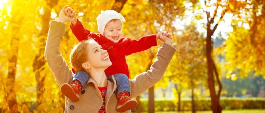 Mama und Kind freuen sich über Herbst