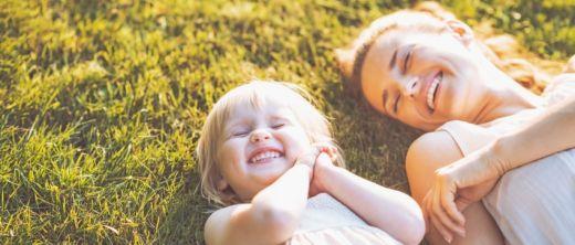 Mutter und Kind liegen im Gras