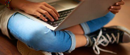 Mädchen mit Laptop auf dem Schoss