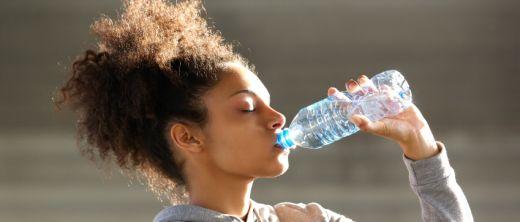 junge frau trinkt wasser aus plastikflasche
