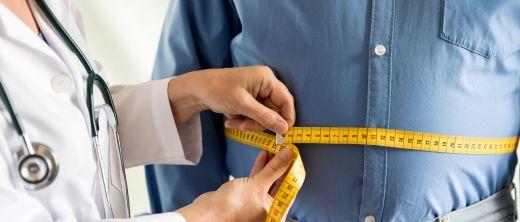 Arzt misst Bauchumfang eines übergewichtigen Patienten