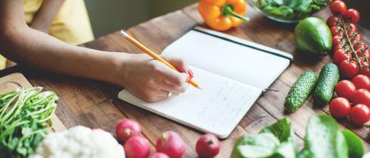 Frau schreibt in Notizbuch, was sie gegessen hat