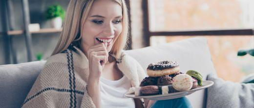Junge Frau sitzt mit Teller voller Backwaren auf dem Sofa