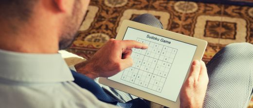 Mann löst Sudoku auf Tablet