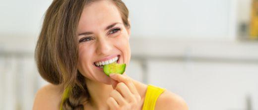 Frau isst Gurkenscheibe