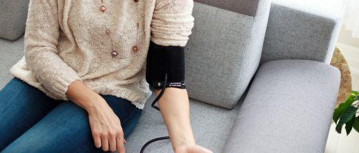 Frau misst ihren Blutdruck