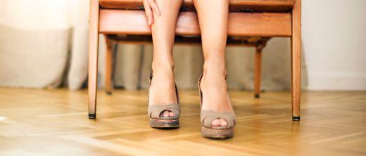 Frau hat hohe Schuhe ausgezogen