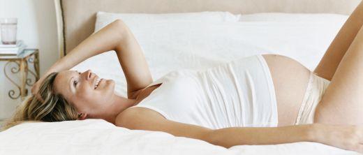 Schwangere Frau liegt auf Bett