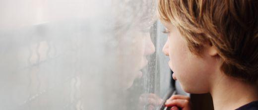 Junge schaut abwesend aus einem beschlagenen Fenster und träumt in seiner Welt vor sich hin.