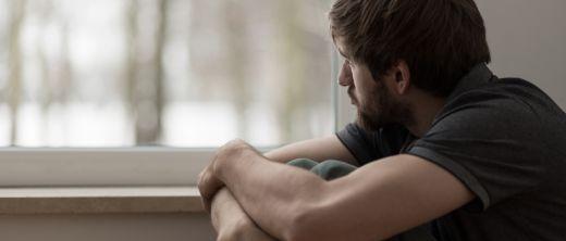 Mann blickt traurig aus dem Fenster