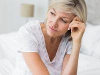 Frau sitzt auf Bett und ist bedrückt