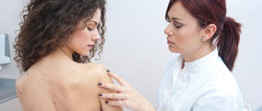 Ärztin untersucht Haut einer Frau