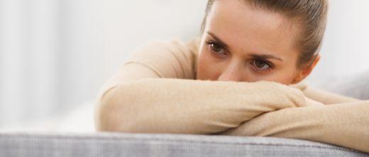 Frau sitzt traurig auf Sofa/Couch
