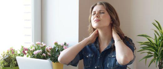 Junge Frau sitzt vor dem Computer und hat Nackenschmerzen
