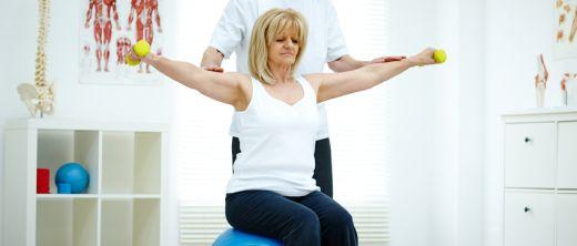 Frau sitzt mit Physiotherapeuten bei der Ergotherapie