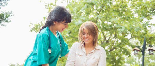 Ergotherapeutin übt das Laufen an Gehhilfen / Krücken mit einer jungen Patientin