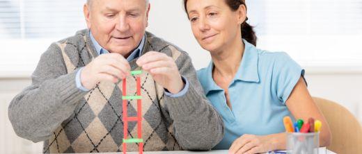 Älterer Mann baut Turm aus Holzklötzchen in der Ergotherapie