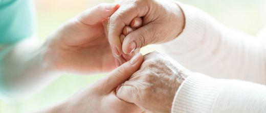 Palliativärztin hält Hand von Patientin und spendet Trost