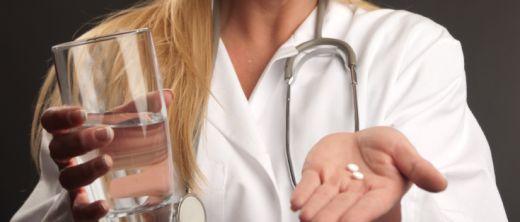 Ärztin gibt Patienten Kopfschmerztabeltten