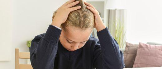 Kind macht Hausaufgaben und hat Kopfschmerzen
